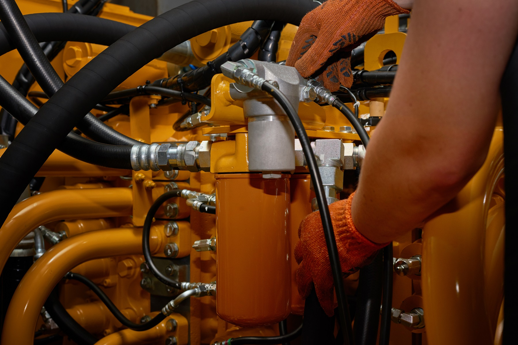 Low key photo of hydraulic pipes maintenance on heavy industry machine.
